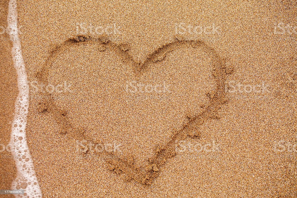 Heart on sand taked by waves royalty-free stock photo