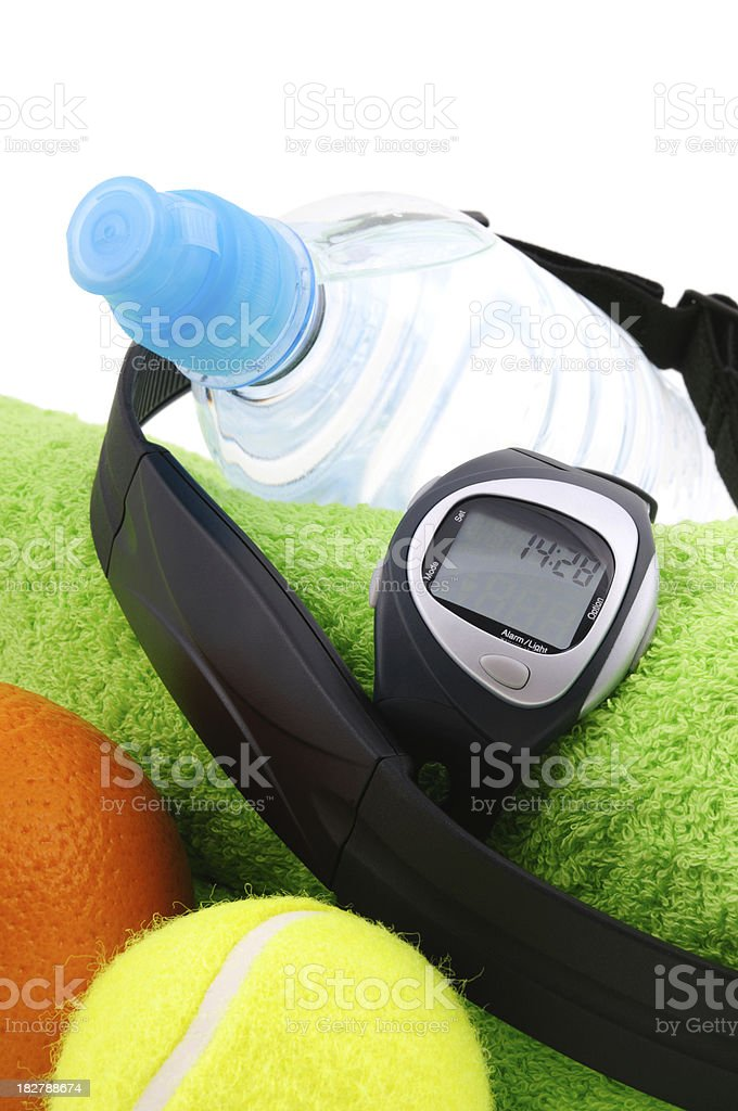 Heart rate monitor, tennis ball, orange, bottle of water royalty-free stock photo