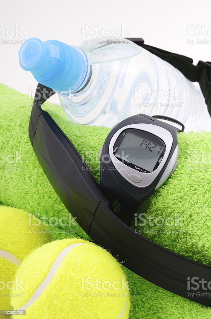 Heart rate monitor, tennis balls, bottle of water and towel royalty-free stock photo