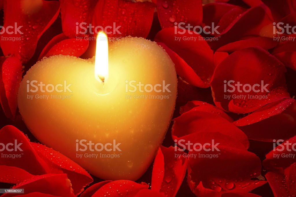 Heart shape candle and rose petals royalty-free stock photo