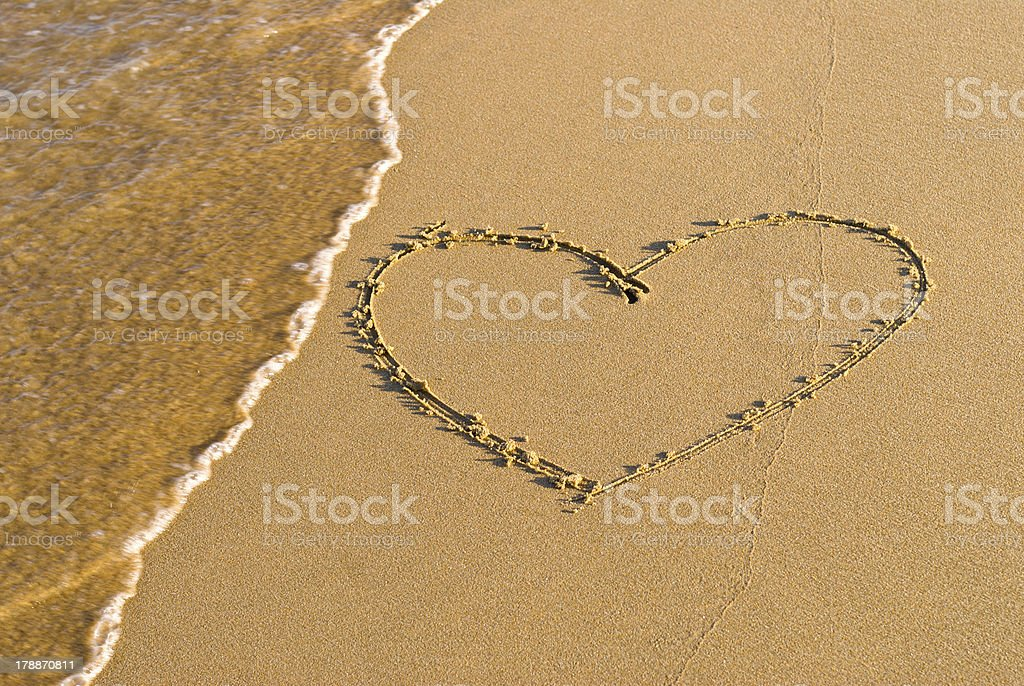 Heart shape drawing in the sand stock photo