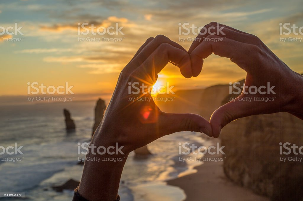 Heart shape finger frame at sunset to the Twelve Apostles stock photo