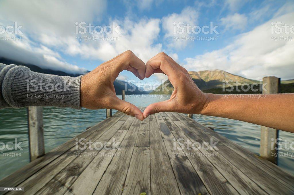 Heart shape finger frame on beautiful landscape stock photo
