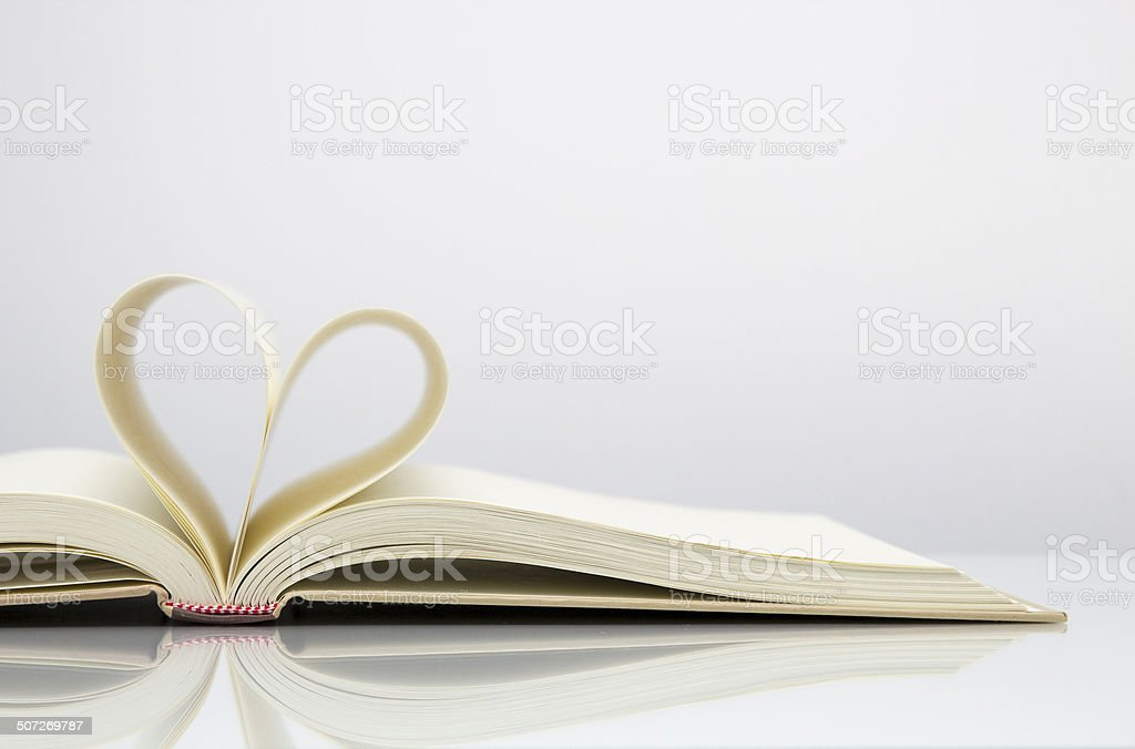 Heart shape from open book page stock photo