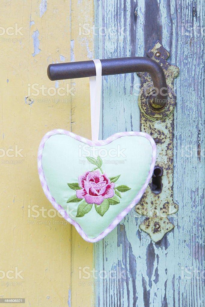 Heart shape hanging on rusty door handle for valentine. stock photo