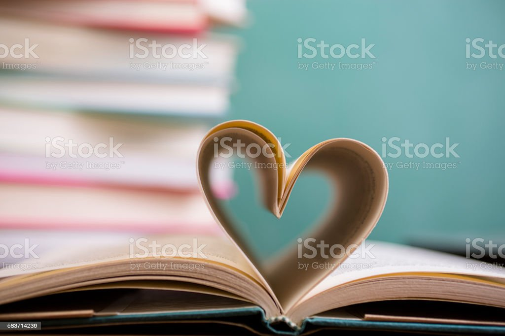 Heart shape in open school book pages. stock photo