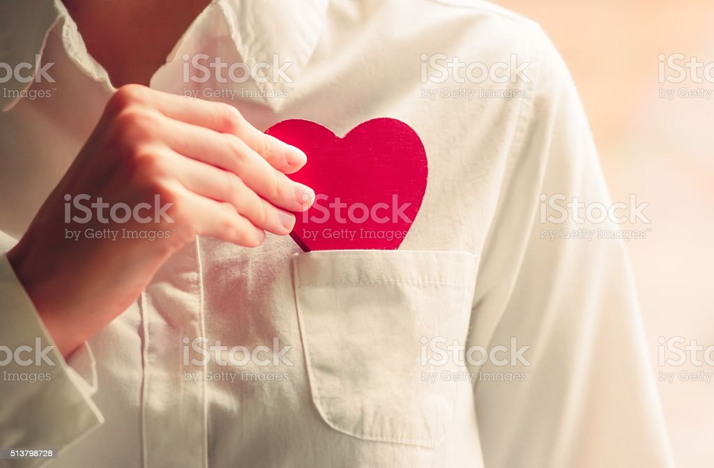 Heart shape love symbol in woman hands stock photo