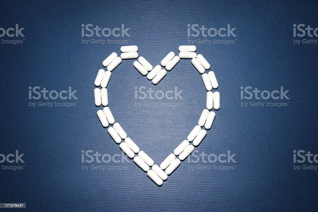 heart shape made with white pills against blue background royalty-free stock photo