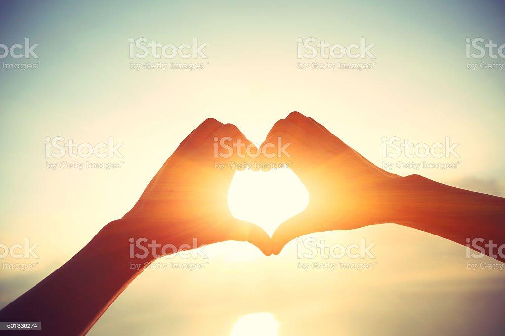 Heart shape making of hands against bright sea sunrise stock photo
