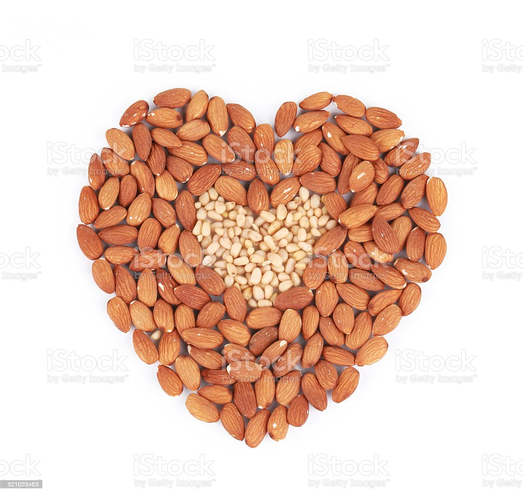 Heart shape of almonds and pine nuts. stock photo