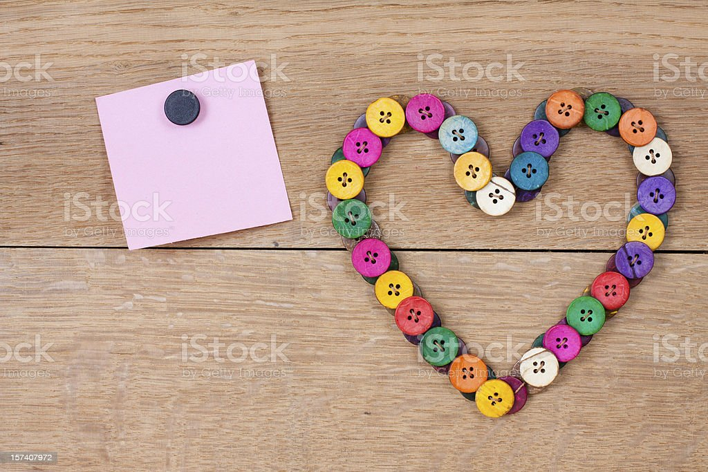Heart shape of color buttons and paper on wooden background royalty-free stock photo