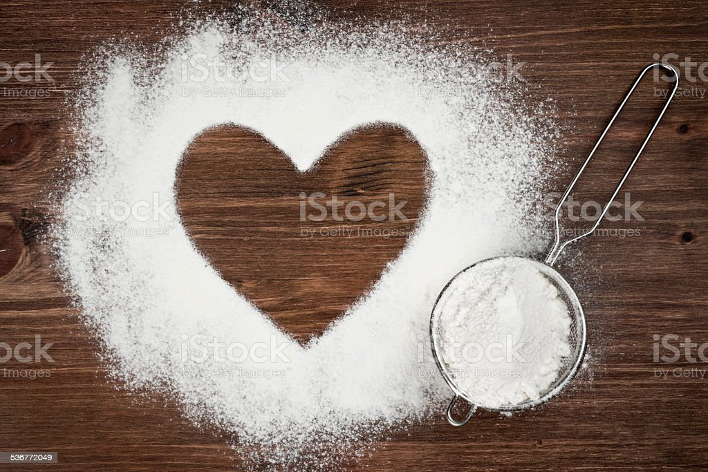 Heart shape of flour on brown wooden board background stock photo