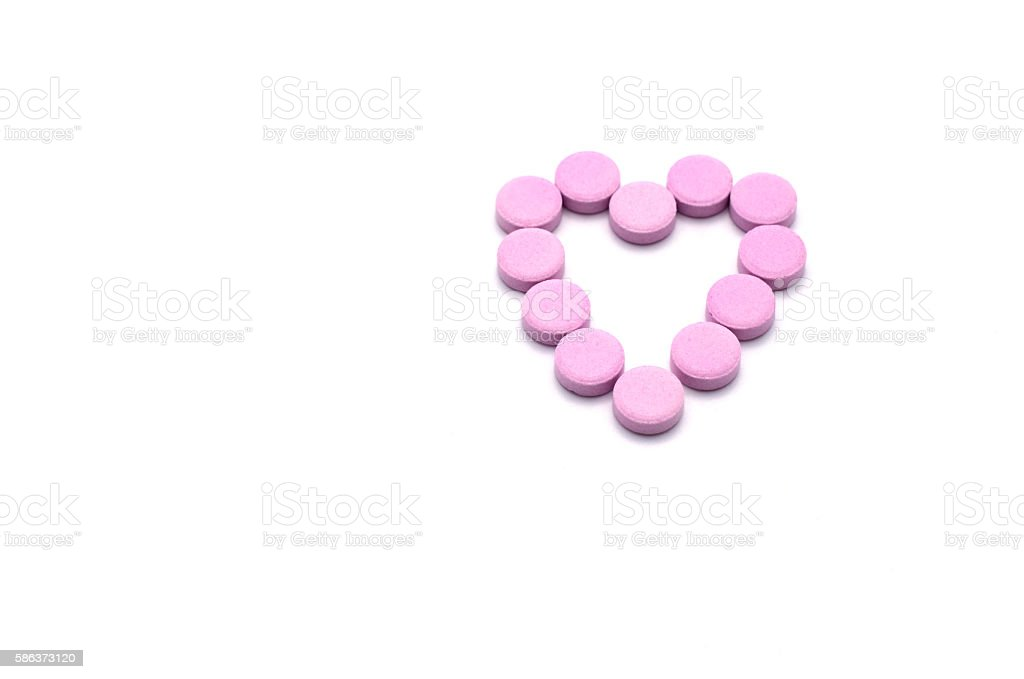 Heart shape of pink pills isolated on white background. stock photo