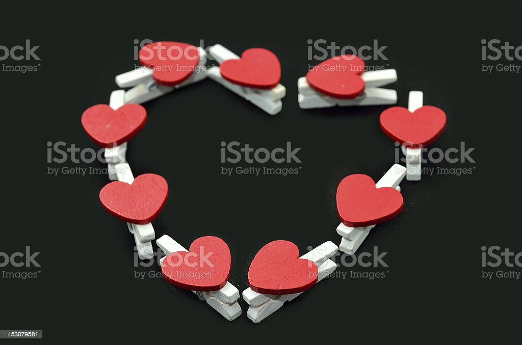 Heart shape of wooden clothes clips mixed on blackground royalty-free stock photo