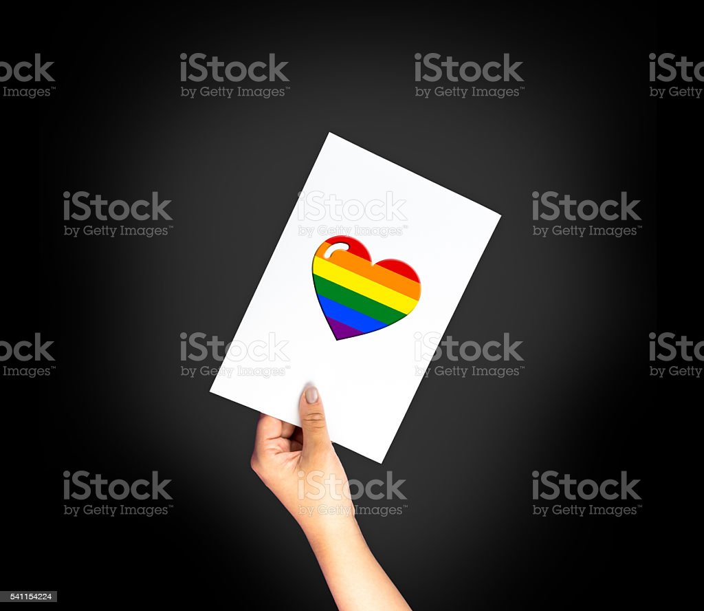 Heart shape on card with hand holding; LGBT color flag stock photo