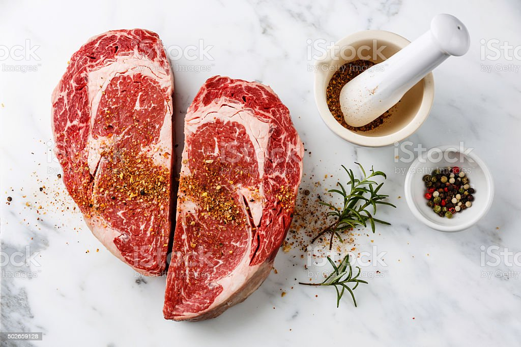 Heart shape Raw meat Ribeye Steak with pepper and rosemary stock photo