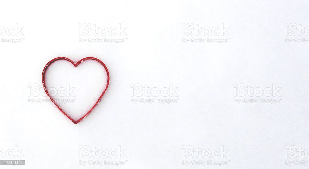 Heart shape red cookie cutter in snow royalty-free stock photo