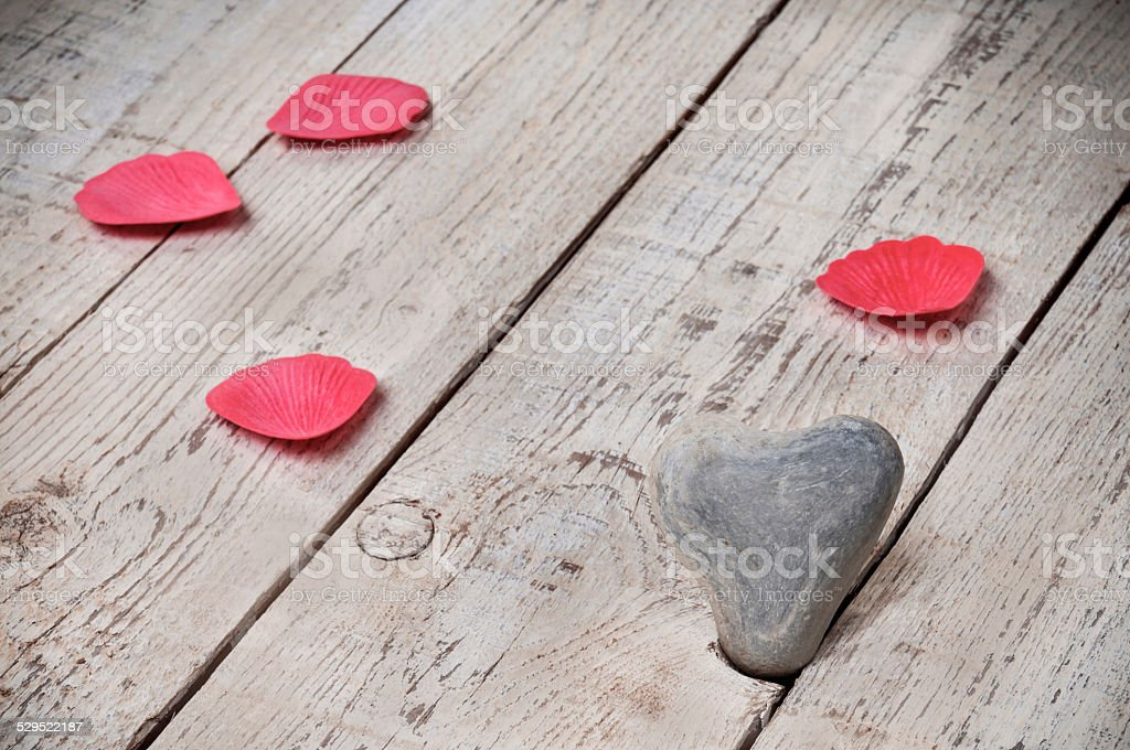 Heart shape stone with rose leaves on blank wood stock photo