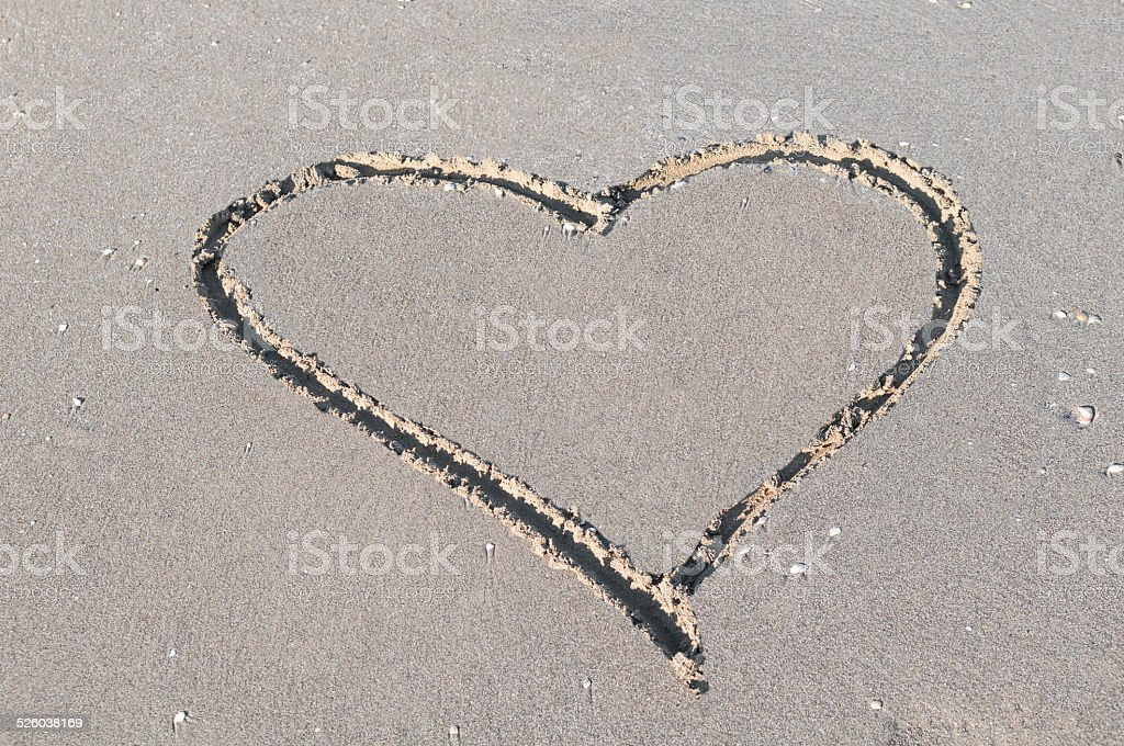 Heart shape traced in sand on a beach stock photo