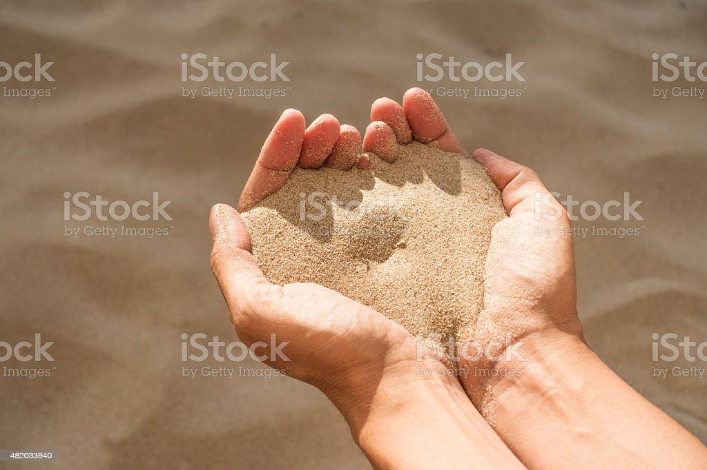 heart shape with handful of sea sand stock photo