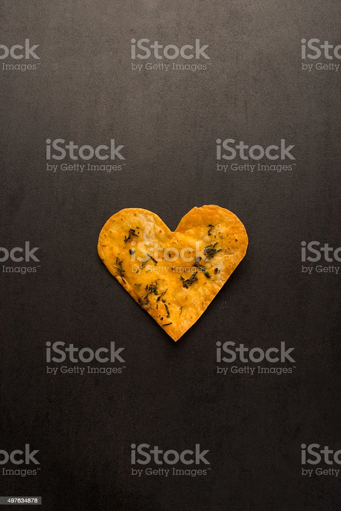 heart shaped biscuit on black stone surface stock photo