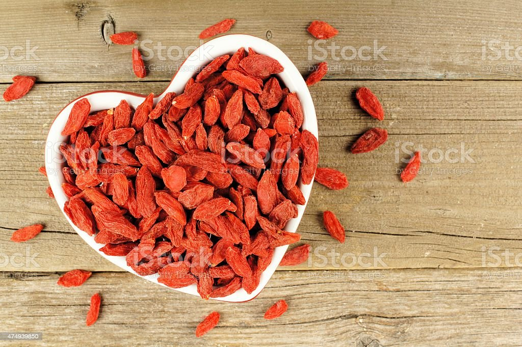 Heart shaped bowl of goji berries on wood stock photo