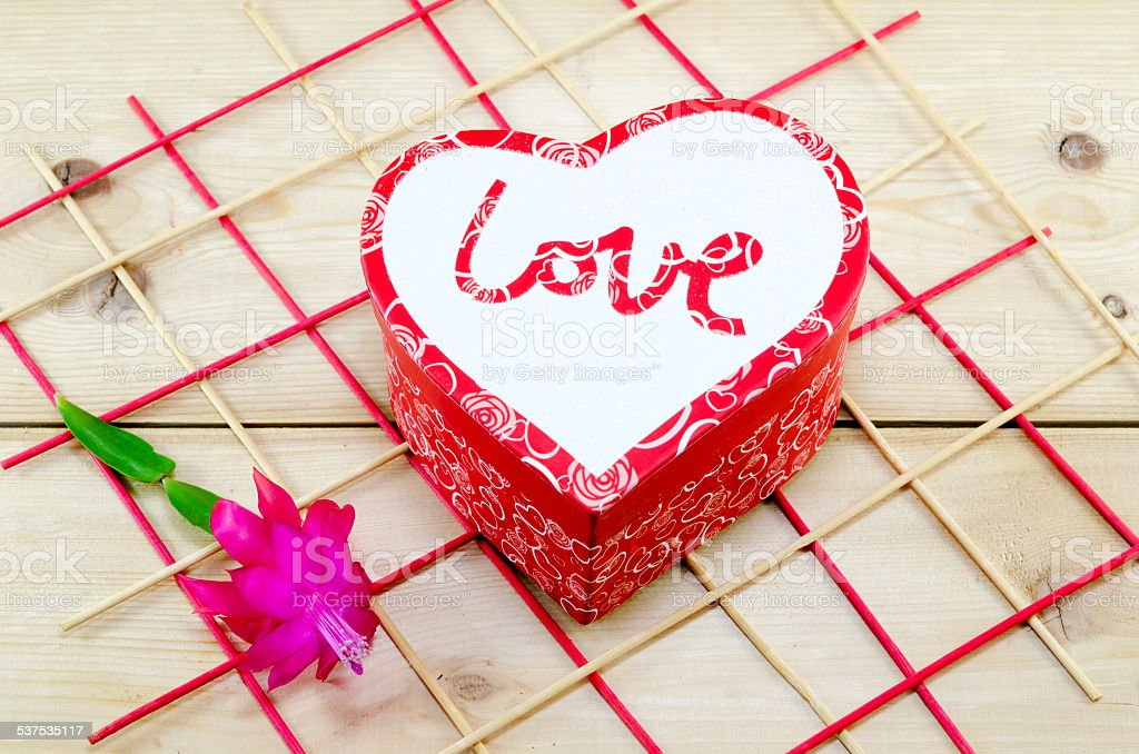 Heart shaped box decorated with a pink flower royalty-free stock photo