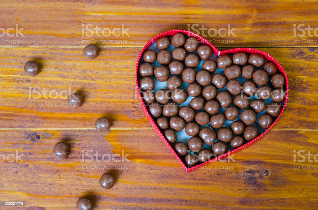 Heart shaped box filled with small chocolates balls royalty-free stock photo