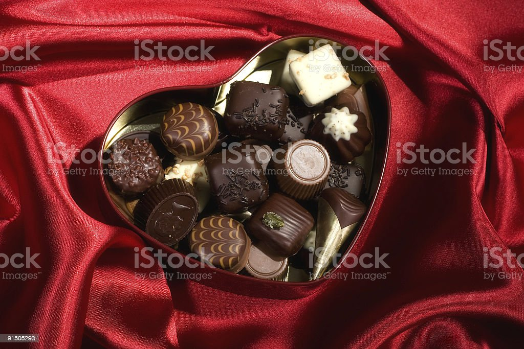 Heart Shaped Box of Candy on red satin background royalty-free stock photo