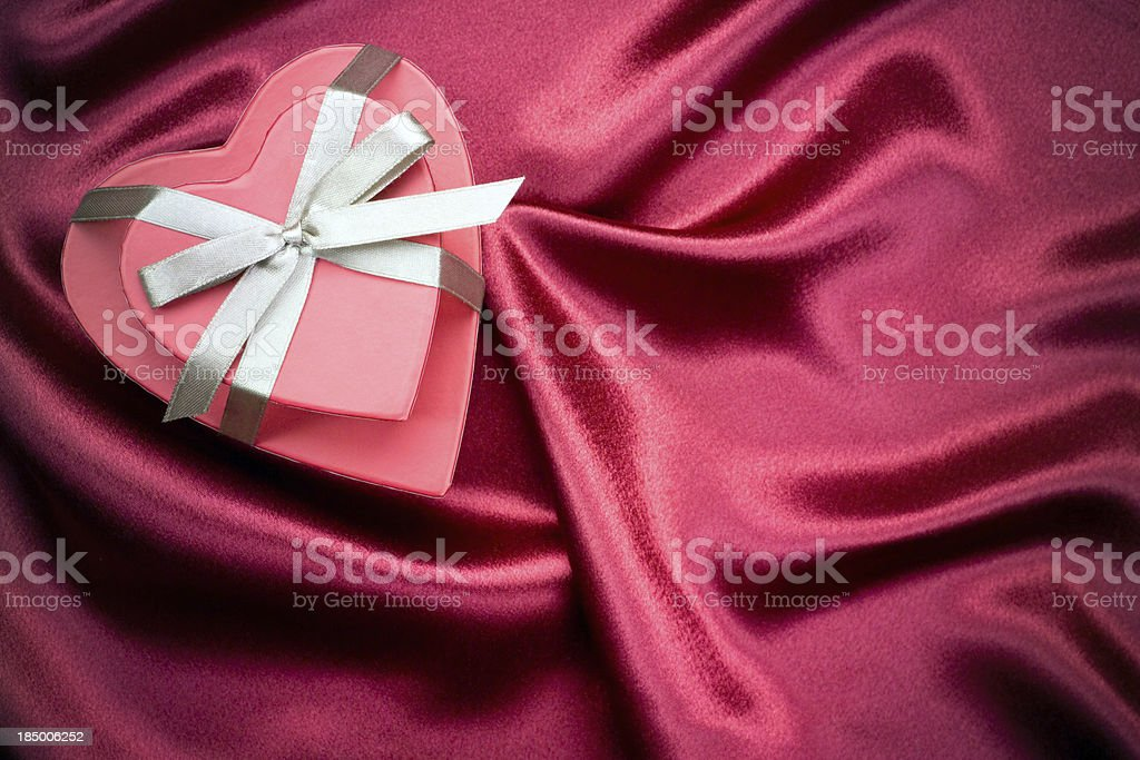 Heart shaped boxes with bow on red satin background stock photo