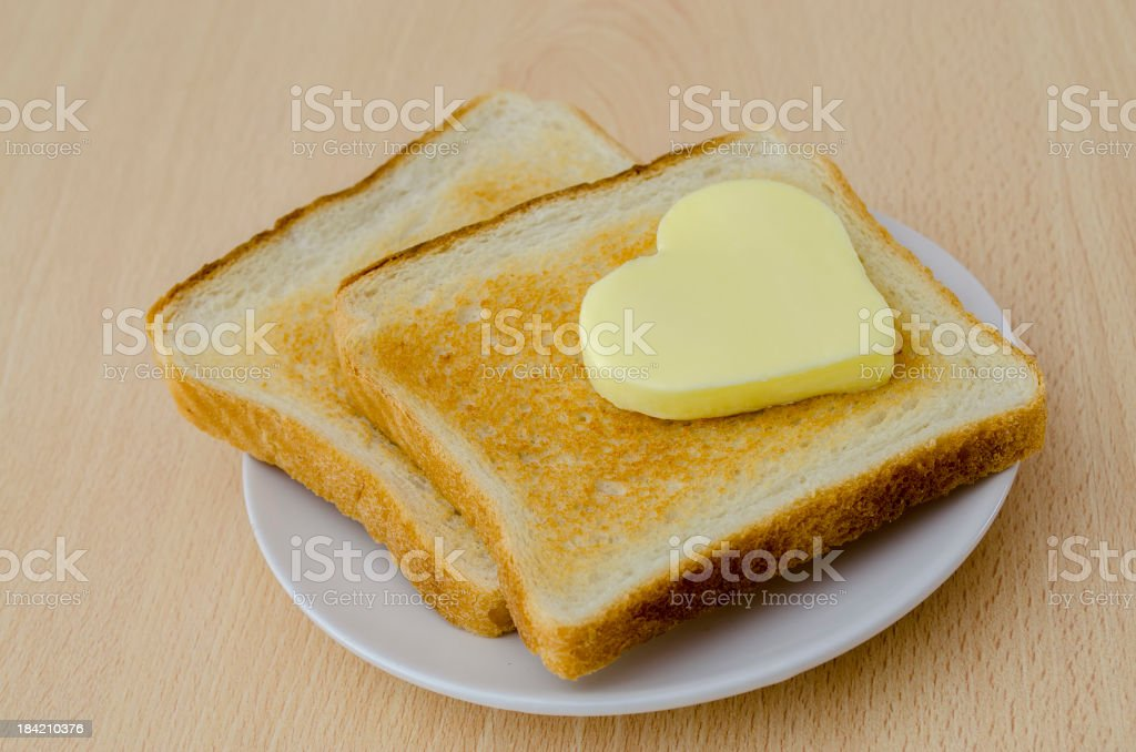 Heart shaped butter on freshly toasted bread stock photo