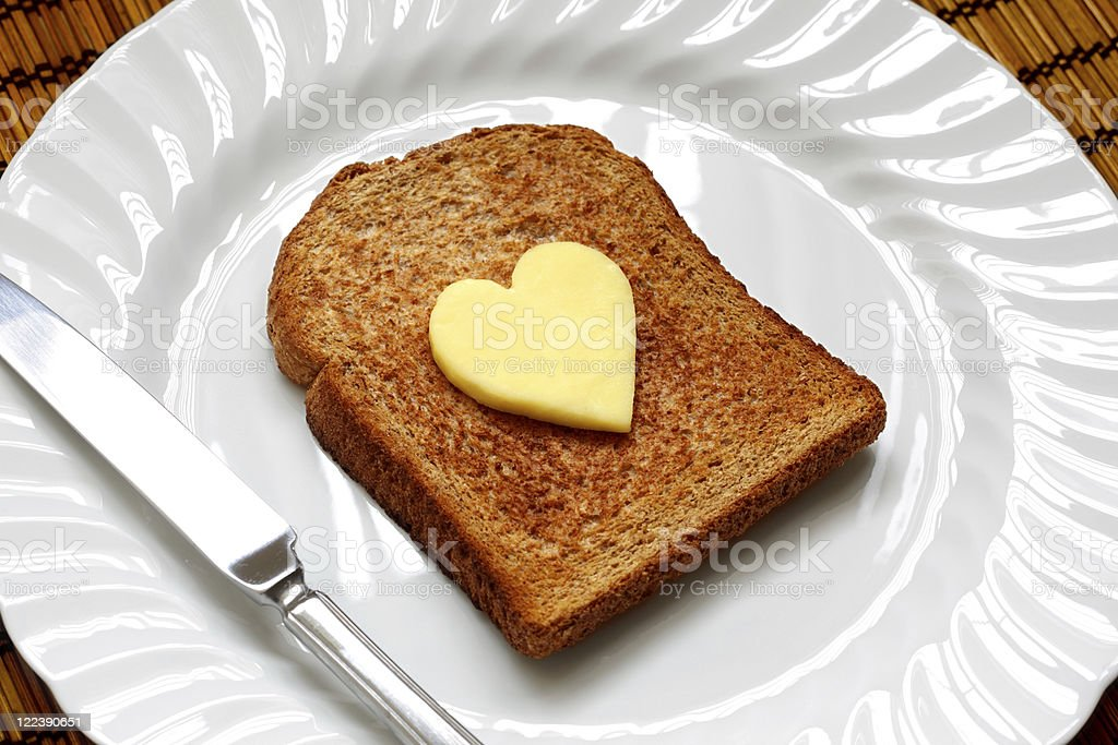 Heart shaped butter on toast stock photo