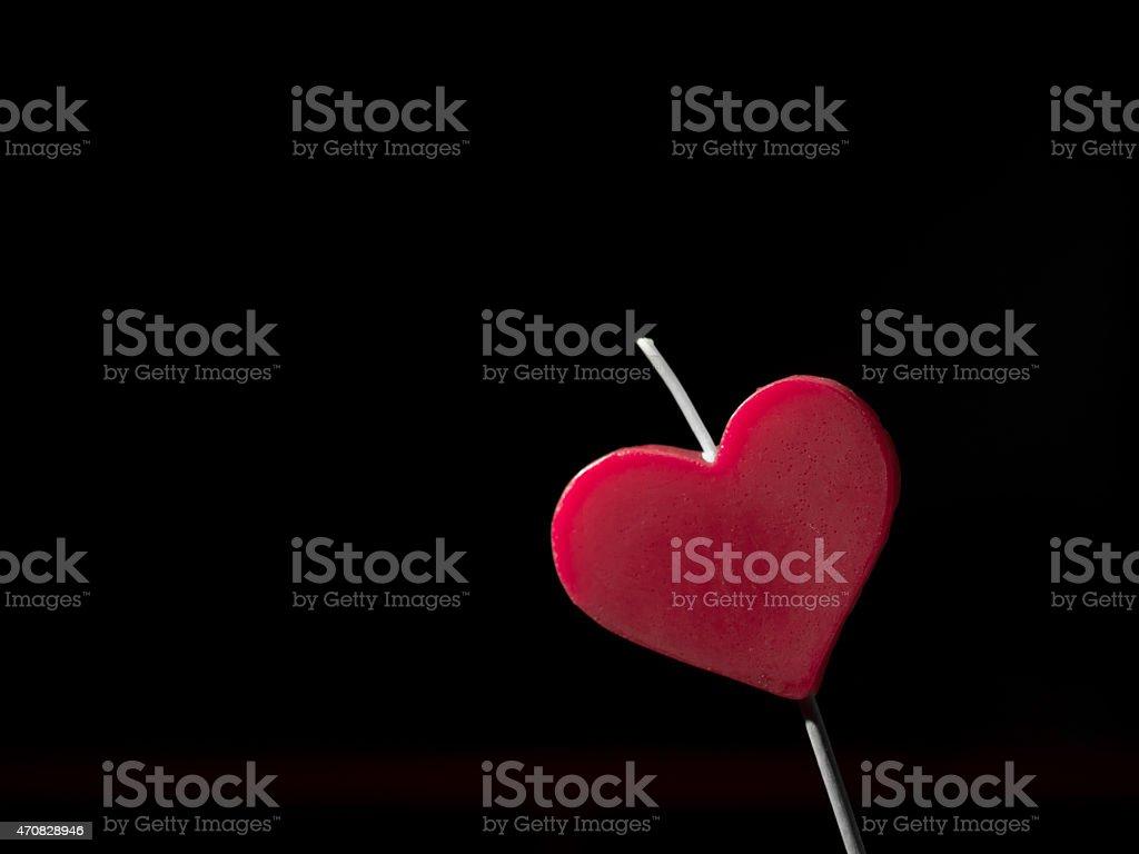 Coração em forma de vela. Fundo preto foto royalty-free