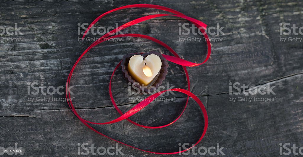 Heart shaped candle on the wooden table with red ribbon royalty-free stock photo