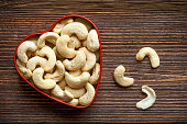 Heart shaped cashew nuts on wooden background