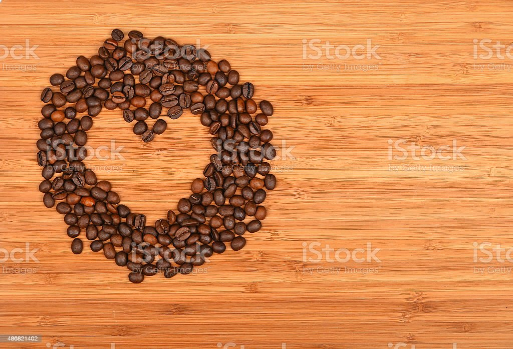 Heart shaped coffee beans frame over bamboo wood background royalty-free stock photo