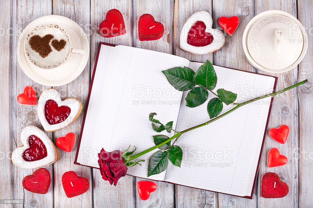 Heart shaped cookies with empty notebook on rustic wooden table. stock photo