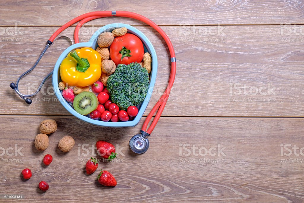 Heart shaped dish with vegetables and stethoscope isolated on wo stock photo