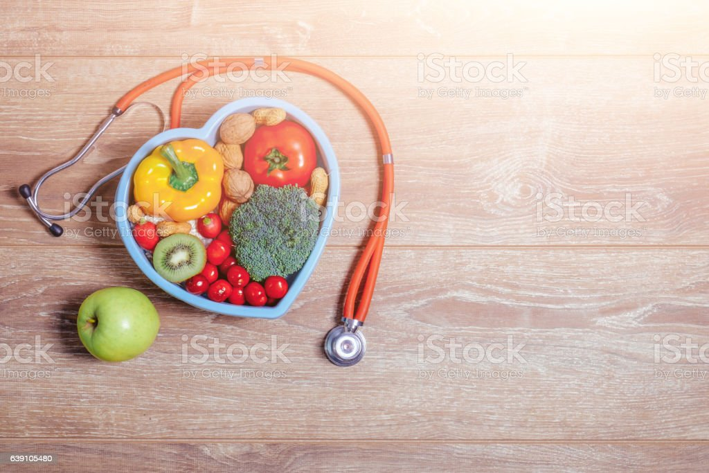 Heart shaped dish with vegetables and warm sun flare stock photo