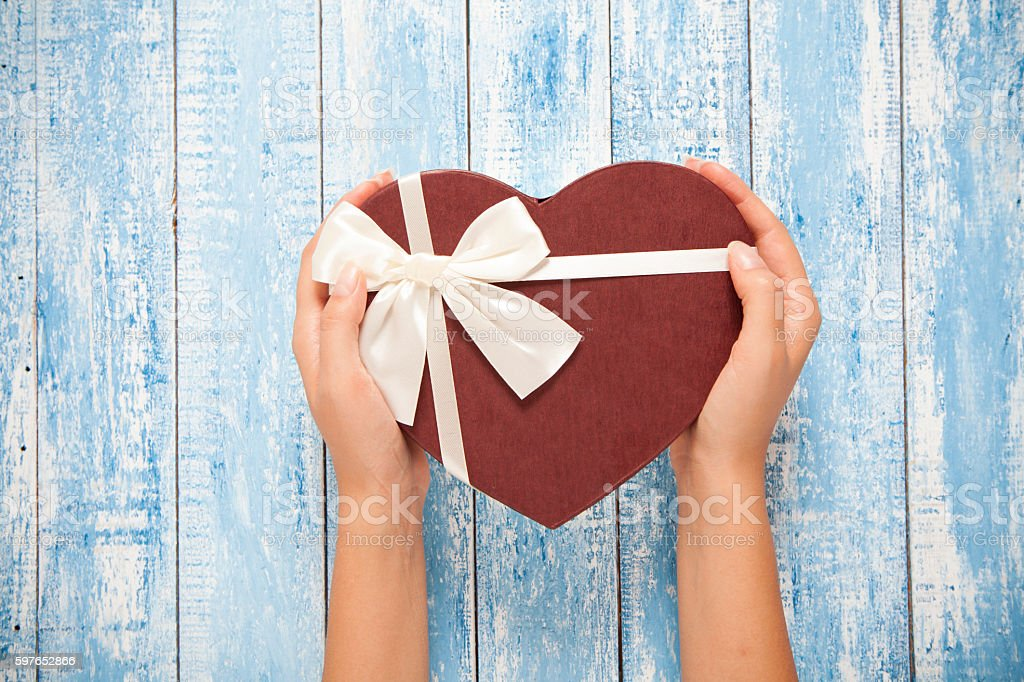 Heart shaped gift box in woman's hands stock photo