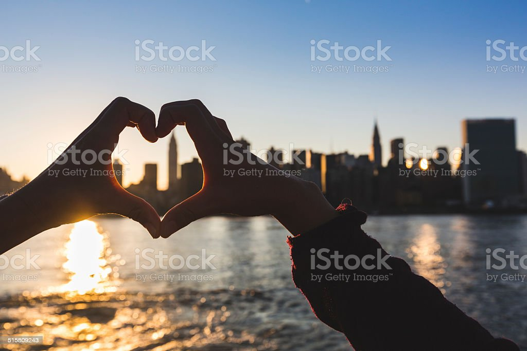 Heart Shaped Hands at Sunset, New York Skyline on Background stock photo