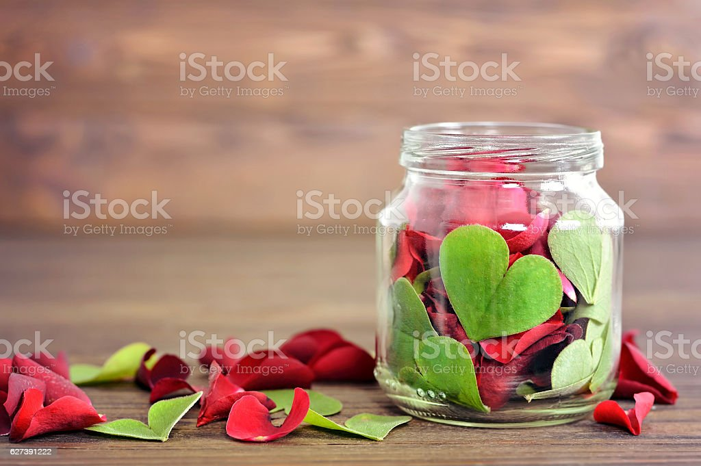 Heart shaped leaves and rose petals in the jar stock photo