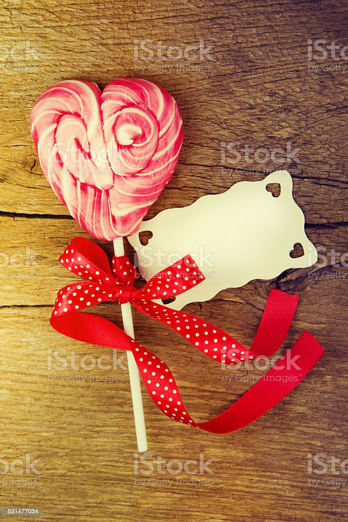 Heart shaped lollipop for Valentine's Day with wooden background. stock photo