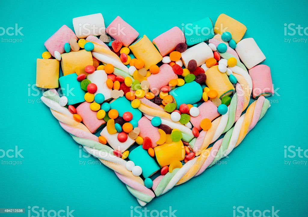 Heart shaped marshmellows candy on blue background stock photo