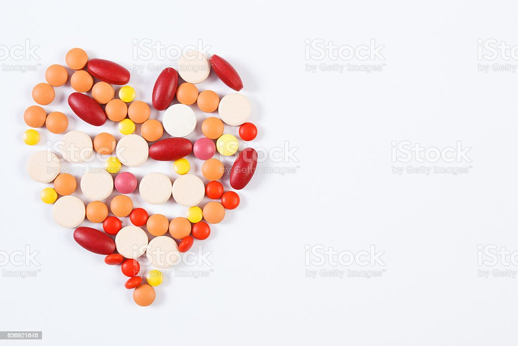 Heart shaped medical pills and capsules on white background stock photo