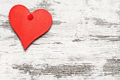 Heart shaped note on white weathered wooden wall