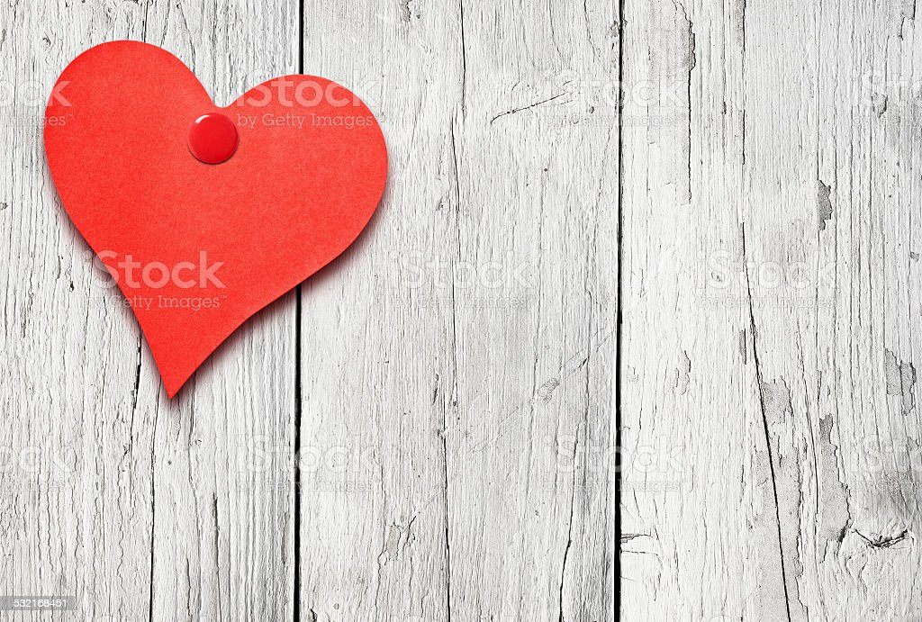 Heart shaped note on white wooden wall stock photo