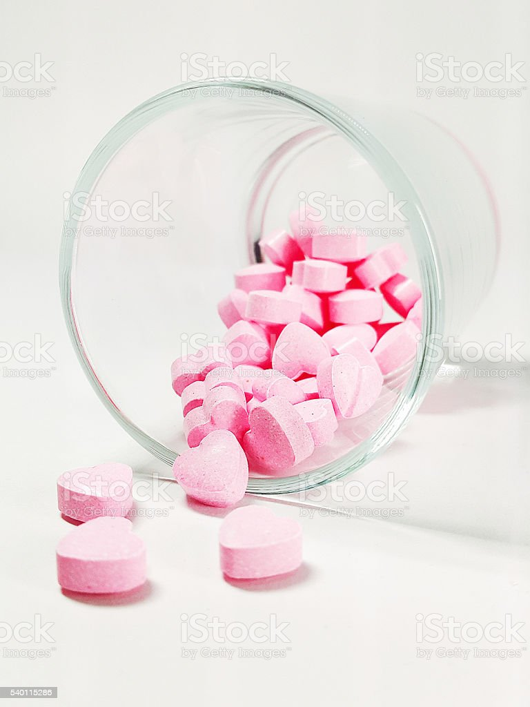 Heart shaped pills coming out from the tilted glass stock photo