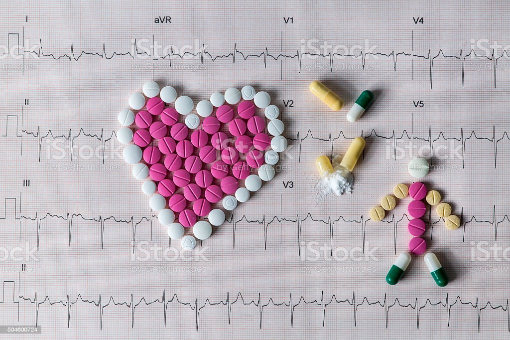 heart shaped pills on a heartbeat stock photo