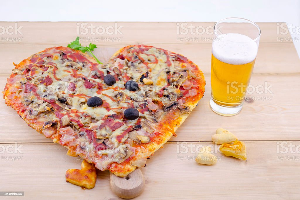 Heart shaped pizza and a glass of beer royalty-free stock photo